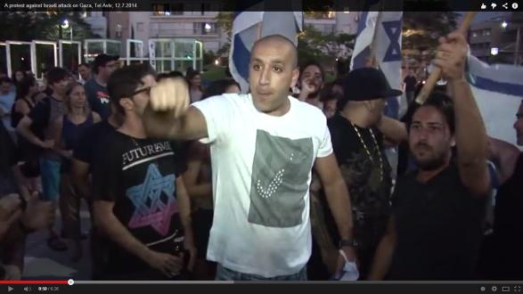 חולצה עם כיתוב ברור של פוטוריזם ומגן דוד בסגנון פוטוריסטי בהפגנה בהבימה מלחמה 2014